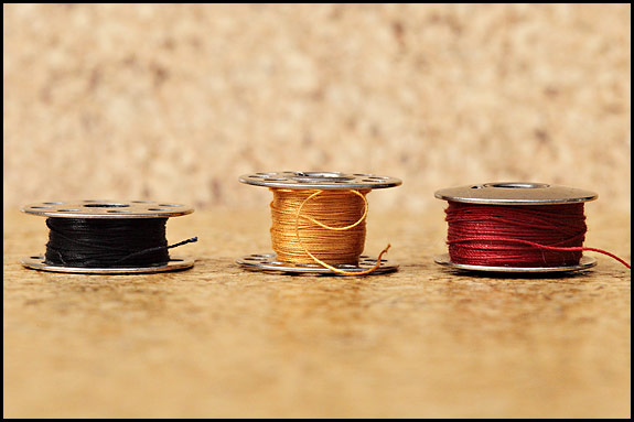 Side view of three different vintage Singer bobbins